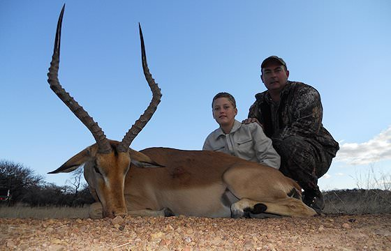 A professional hunter sits alongside a young hunter and his impala trophy.