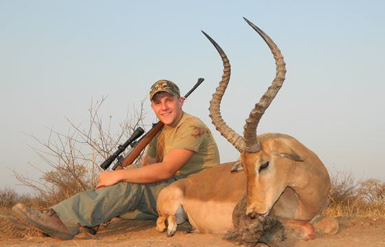 A proud hunter relaxes next to his impala trophy.
