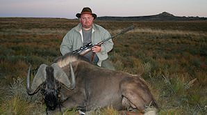 A hunter kneels behind his black wildebeest trophy.