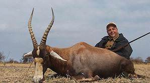 A huntress poses with her bontebok and professional hunter.