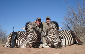 Twin zebra trophies are posed for a photograph with their two hunters.