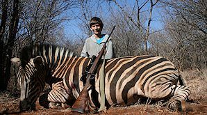 A young hunter sit proudly behind his Burchell's zebra trophy.