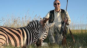 A hunter smiles with his Burchell's zebra trophy.