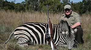A hunter poses with his zebra.