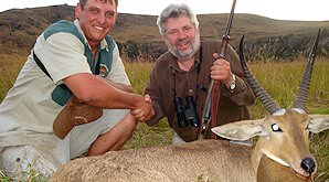 A hunter shakes hands with his professional hunter alongside their reedbuck trophy.