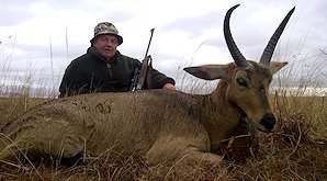 A hunter sits alongside his common reedbuck trophy.