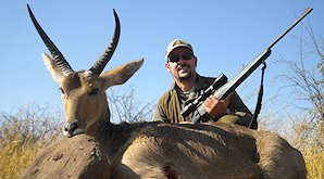 A hunter sits behind his common reebuck trophy.