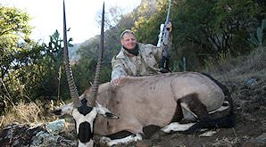 A gemsbok trophy is presented for a commemorative photograph.