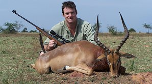 A hunter poses with his rifle and his impala trophy.