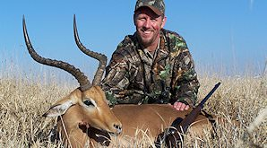 An hunter presents his impala trophy for a photo.