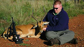 A hunter sits down alongside his impala trophy.
