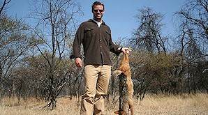 A hunter presnts a jackal trophy for a photograph.