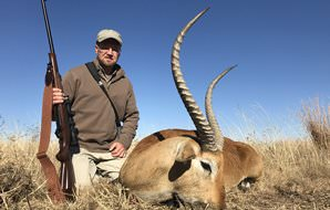 A hunter crouches down next to his red lechwe trophy.