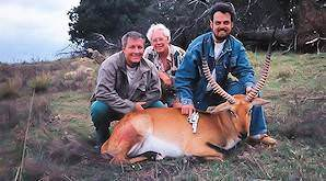 A team of hunters present a lechwe trophy for a photo.