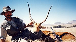 A hunter smiles proudly alongside his red lechwe trophy.