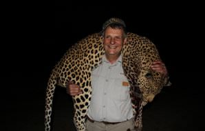 A hunter drapes his leopard trophy over his shoulders.