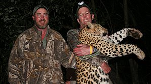 A hunter with his leopard trophy and professional huner.