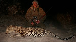 A hunter smiles with his leopard trophy.