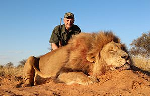 A hunter smiles with his lion trophy in the Kalahari.