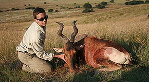 A young hunter props up his red hartebeest trophy for a photograph.