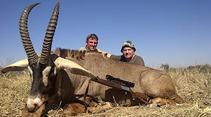 A hunter with his PH and roan antelope trophy.