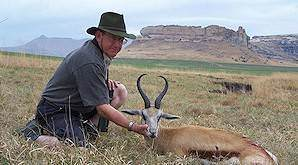 A hunter holds up his springbok trophy.