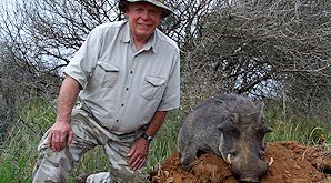 A hunter smiles alongside his warthog trophy.