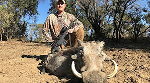 A hunter crouches down alongside his warthog trophy.