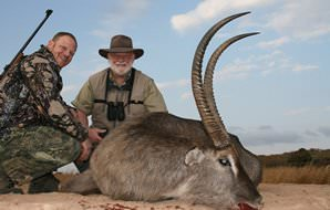 A pair of hunters smile with their waterbuck trophy.