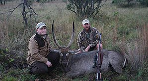 Two hunters sit alongside their waterbuck trophy.