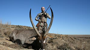 A huner stands behind his waterbuck trophy.