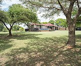 Lush lawns and thorn trees surround this bushveld hunting camp.