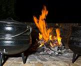 A potjie next to a fire at a rest camp.
