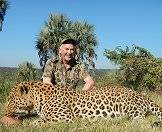 A hunter sits triumphantly alongside his leopard trophy.