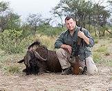 A hunter poses with a black wildebeest.
