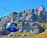 A cable car approaches the facade of Table Mountain.