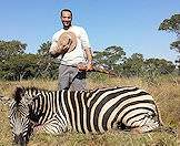 A hunter smiles with his zebra trophy.