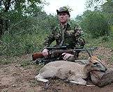 A hunter positions his grey duiker trophy for a memorable photograph.