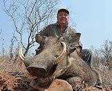 A hunter smiles above his warthog trophy.