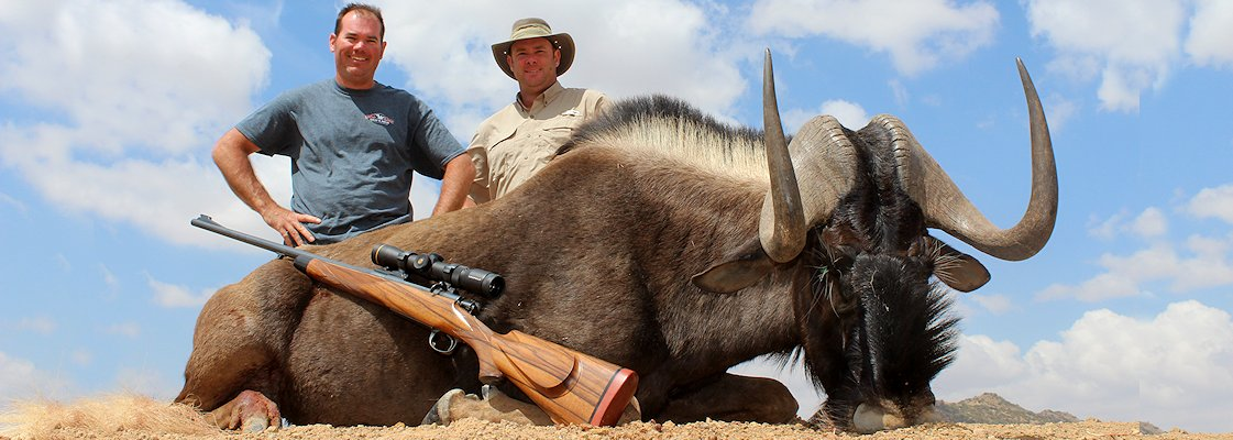 A hunter smiles proudly with his black wildebeest trophy and professional hunter.