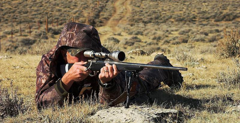 A hunter looks through his scope and prepares to fire his rifle.