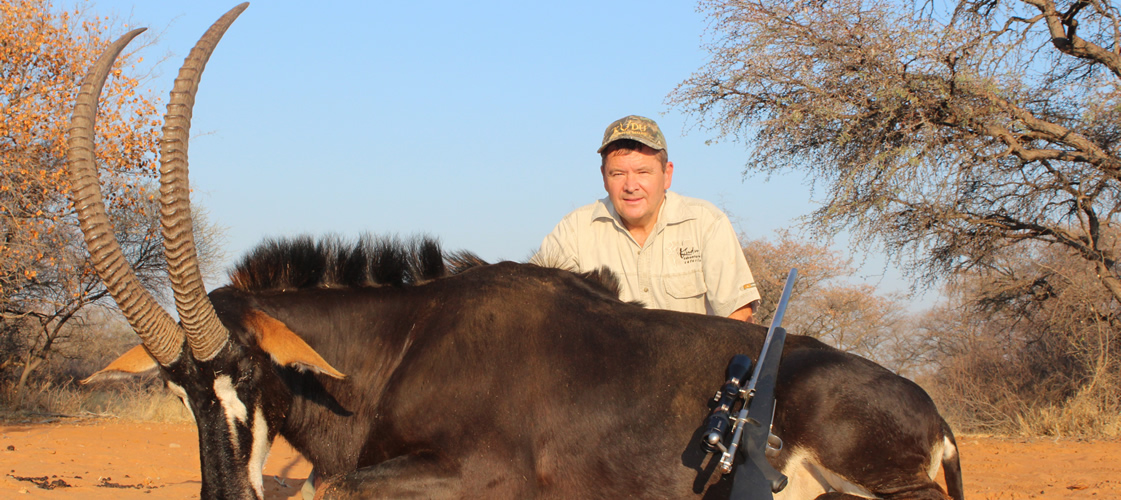 A hunter sits behind his impressive Sable antelope trophy.