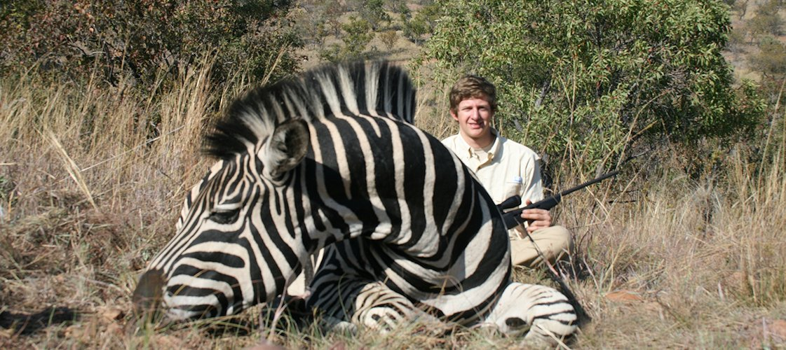 A proud hunter with his Burchell's zebra trophy.