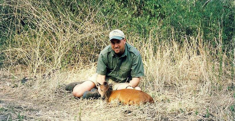 A hunter presents his red duiker trophy for a photograph.