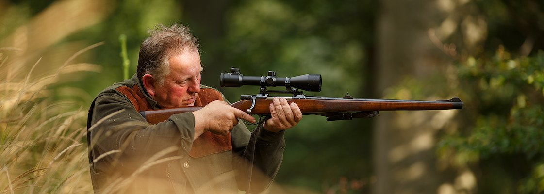 A hunter prepares to take a shot with his rifle.